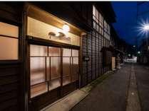 宿前の通り、小路の両側には町家が並びます。通りの向こうには尾﨑神社の朱色の板塀が見えます。