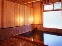 レンガ色のタイルと木のあたたかみを楽しむ浴室(写真:冨田治)