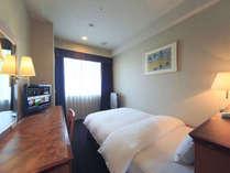 シングルルーム(16平米)ベッドにはシモンズ社製デュベを採用。液晶TV完備。ユニットバス。
