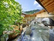 【庭園露天風呂】庭園大露天風呂では大岩と季節の花を眺めながらご入浴いただけます。