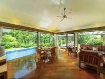 【デラックスコテージ】開放的なリビングルームは窓から緑が綺麗に見えて南国を感じることができます。