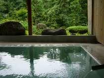 [写真]露天風呂(女性用)。庭の景観を眺めながら格別の湯浴みを