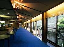 【ロビー】桂川に架かる橋の上で、窓いっぱいに広がる景色を眺めながらチェックイン