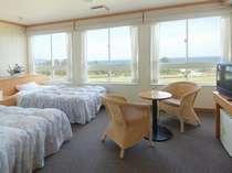 【海側DXツイン一例】ベッドはセミダブル。窓からはきらきら光る海がご覧いただけます。