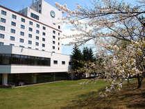 【春の外観】中庭に咲き乱れる桜がホテルを装ってくれます。
