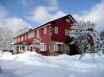 雪景色に映えるレンガ色の洋館