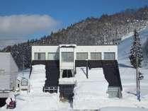 建物はスキージャンプ台(シャンツェ)の形。裏はノルディックコース、前の道路400m先が栂池スキー場駐車場