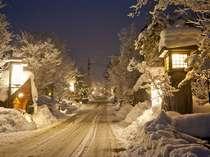 福地温泉の冬の夜。真っ白な景色に宿看板の明かりが浮かび上がる。幻想的な光景です。