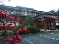 秋深まり、潅木の真っ赤に染まった実と共に映る外観