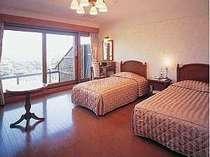 本館ツインルームの一例。大きな窓の向こうには雄大な海の景色が広がる。
