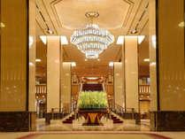 吹き抜けの天井にかかるゴールデンローズのシャンデリアと季節の花々がお客様をお迎えいたします。