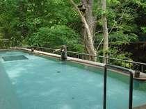 渓流を望む混浴野天風呂。近くの木にはムササビの巣箱。「ぬる湯の長湯が鹿教湯の湯」。