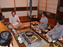 囲炉裏を囲んで仲間たちでわいわいと楽しむ夕食。鍋や五平餅、いわなは絶品。