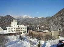 ◆冬の東大雪山系をバックに佇むホテルの全景