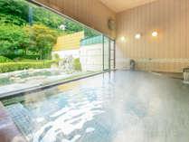 *【大浴場/内湯】全面ガラス張りの空間。大きな窓の外には、露天風呂のスペースと、裏山の緑が広がります