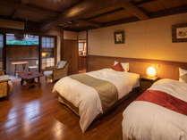 別館『えにし』洋室。ベッドは3台まで増設可。スタイリッシュでありながらも大きな梁が黒川温泉らしい風情