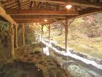 紅葉の渓谷を望む天然岩風呂