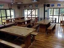 木のテーブルと椅子が並ぶ食堂。お食事はこちらで。薪ストーブで冬も暖かい!