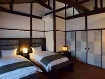 天井に大きな梁が横切る寝室。間接照明でやわらかな光に包まれ、ゆったりお休み頂けます。