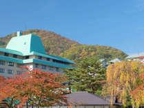 【ホテル花巻】秋の外観。紅葉した木々に囲まれます。
