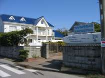 サーフボードの看板が目立つ、青い屋根と白い壁のペンション。