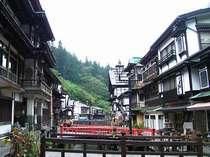銀山温泉街。当館の目の前にある足湯や、ニジマスが泳ぐ川など、風情あふれる温泉街です。