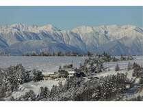 北アルプス連峰の山々を背後にして山頂にある冬のふる里館の全景です。