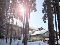 太陽に照らされた雪山の温泉宿。宿の背後には真っ白なスキーゲレンデが広がる。