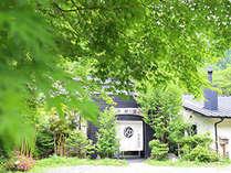 春は桜、夏は新緑、秋は紅葉と、森の緑にすっぽり包まれる小さな民宿。冬は暖炉でおもてなし。