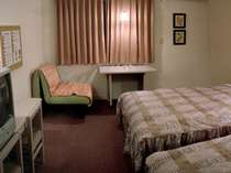 バストイレを含め25平米の広さに、幅1.5m超の大型ベッドが2台。全室ネット無料接続可。