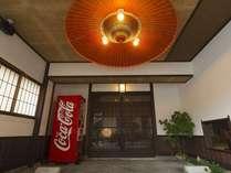 正面玄関には朱塗りの大きな和傘が吊り下げられている。みなさんのお越しをお待ちしています。
