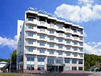 青空広がる大自然に佇む、明るい外観の知床ノーブルホテル。