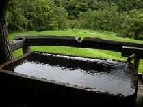 【客室風呂】「長田」の露天風呂は石造り。削り跡が残る湯底は趣深い。7月の景色