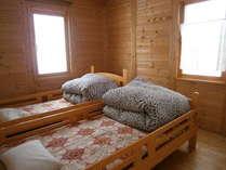ふたつの洋室にはそれぞれベッドが2台完備。窓には広大な牧草畑が広がります。
