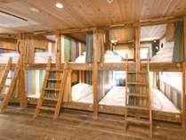 [10名男女混合ドミトリー]カプセルタイプの縦長の2段ベッドで側面は壁で入口はカーテンがあります。