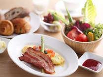 朝食は、地卵料理にベーコン、新鮮野菜のサラダ、焼き立てのパンなど目にも鮮やか