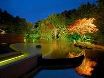 【露天風呂 浮湯】夜は月と星が水面に瞬き、ライトアップの灯りが幻想的な雰囲気を醸して。