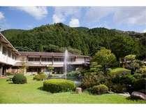 中央の日本庭園を望む二階建ての宿。全客室バス・トイレ付。のんびりくつろぎのひと時を。