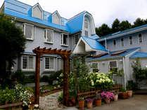 青い屋根にパステルグレーの壁、そして木製アーチが目印
