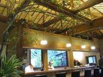 和食処の店内、カウンターとテーブル席、窓の景色はライトアップされた温泉塔が素晴らしい