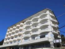 下田海浜ホテル外観青空に生える白い建物、海はコバルトブルー