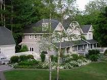 芝生の中庭に面した建物で、お花の咲いているアメリーハウス軽井沢