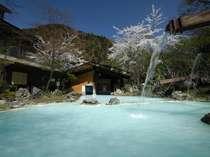 抜けるような春の青空と桜見の露天風呂