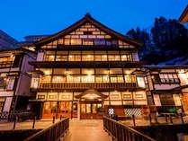 夕暮れの外観。まるで絵のように迫力ある木造3層造りの宿で過ごす贅沢。