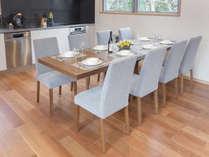 8人掛けの大型ダイニングテーブル に最新設備の揃うおしゃれなキッチン