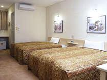 約25平米の広さに幅1.5m超の大型ベッド2台。1名~親子4人まで宿泊可。全室無料ネット接続可。
