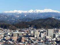 雪化粧の山並みと高山の街並み