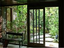 小さいながらも草木で季節感じる坪庭。お庭を通って客室へご案内