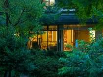 夕闇迫る庭園からロビーを眺めた風景