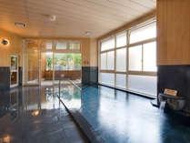 黒御影石を使用した浴槽に道後温泉からの引き湯が満ちる大浴場